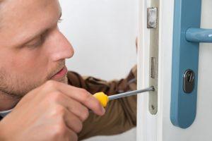41933919 - portrait young male carpenter repairing door lock