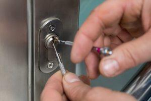 53794744 - close-up of lockpicker hand fixing door handle at home